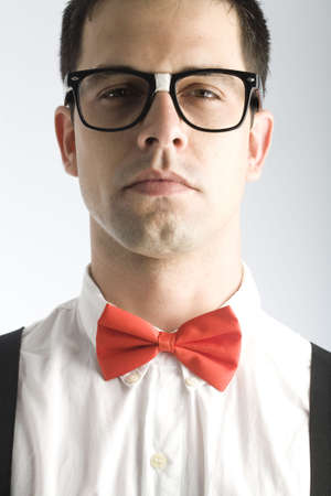 A young, caucasian nerd, close-up, on a light gray background.