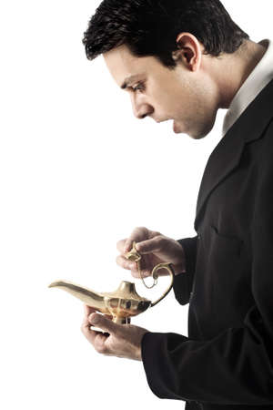 A good looking young business man with a golden magic genie lamp. photo