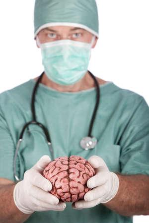 cirujano: Un cirujano 60 a�o de edad, sosteniendo un cerebro, aislado en un fondo blanco.