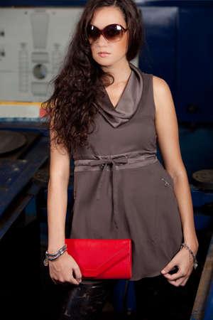 brazilian woman: A young brazilian female model shot in a dirty auto repair shop.