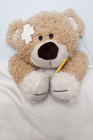 An adorable teddy bear laying in bed, sick, under the sheets.