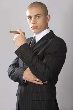 cigar smoking man: A young good looking businessman on a gray background.