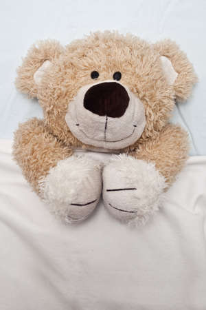 An adorable teddy bear laying in bed, under the sheets. Stock Photo