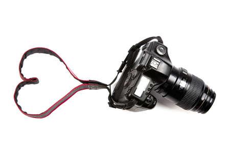 Una fotocamera digitale isolato su uno sfondo bianco, in cui la cinghia fa un cenno cuore. Perfetto per i professionisti e gli amanti della fotografia!