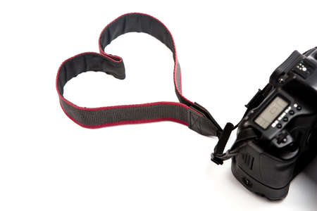 straps: A digital camera isolated on a white background, where the strap makes a heart sign. Perfect for photography professionals and  lovers! Stock Photo