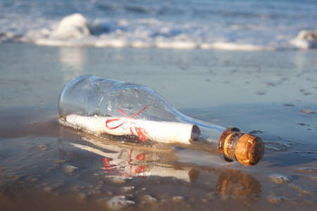 A message inside a glass bottle, washed up on a remote beach. photo