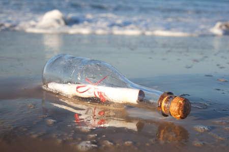Un messaggio in una bottiglia di vetro, lavato su una spiaggia remota.