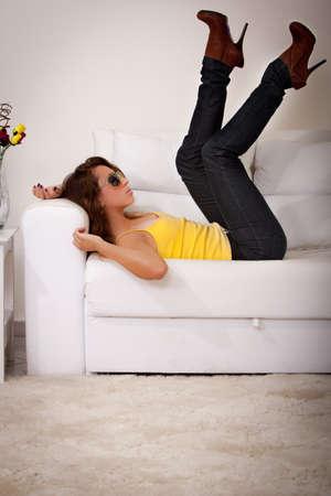 A young brazilian woman wearing a yellow tanktop and yellow sunglasses. photo