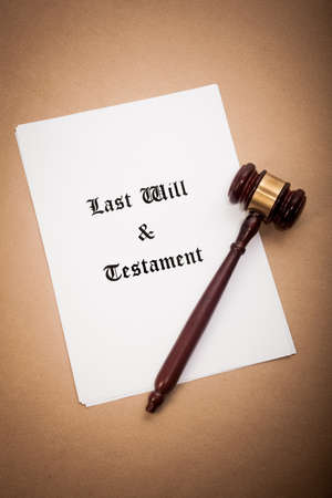 A gavel on top of a Last Will and Testament contract, with a antique-like background. Stock Photo