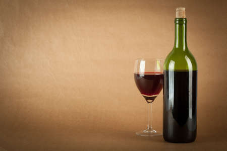 glass half full: A bottle of red wine and a glass half full on a vintage orange background.