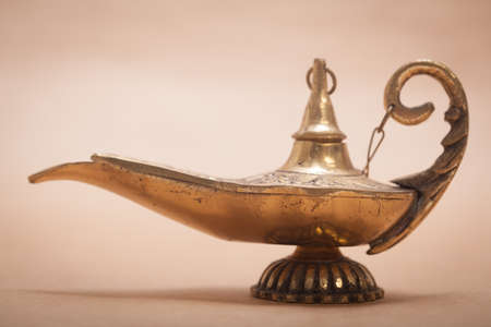 aladdin magic lamp: A magic genie lamp, isolated on a sand color background, in a studio shot.