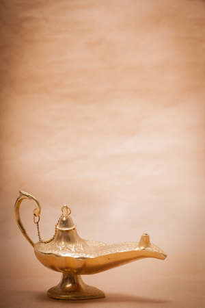 A magic genie lamp, isolated on a sand color background, in a studio shot. photo