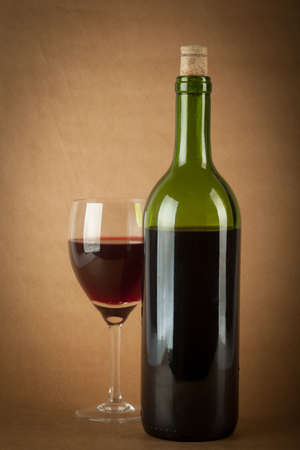 A bottle of red wine and a glass half full on a vintage orange background. photo