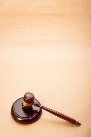 A wooden gavel and soundboard on a light brown background  photo