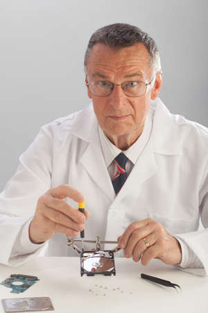 hdd: An older male wearing a white lab coat and repairing electronic equipments, like a technician or a repair man.