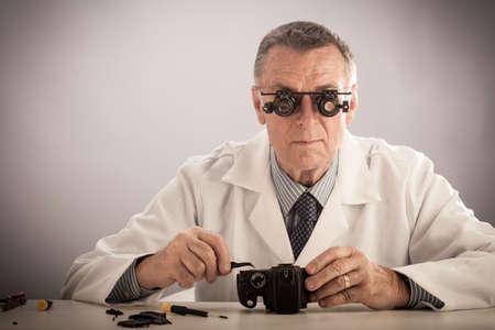 白衣を着て、技術者や修理の人のような電子機器を修復はそれ以上の年齢の男性。