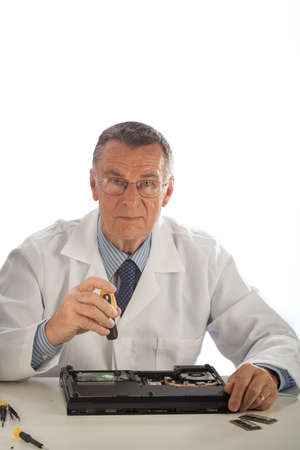 laptop repair: An older male wearing a white lab coat and repairing electronic equipments, like a technician or a repair man.