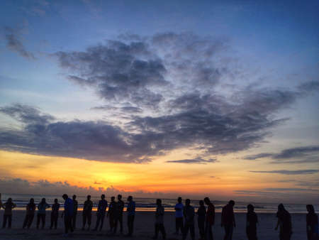 sillouette: sunrise at the beach with people sillouette