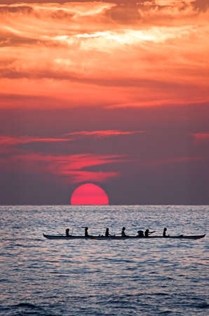 Hawiian women paddling a canoe home at sunset. 免版税图像