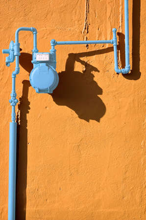 Blue gas meter against a terracotta wall