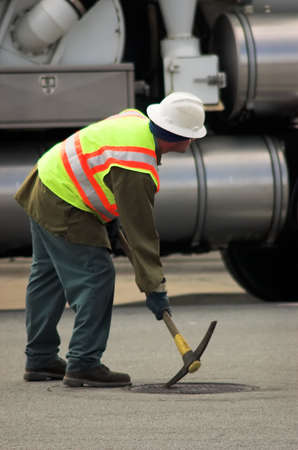 A city workman opening a manhole cover