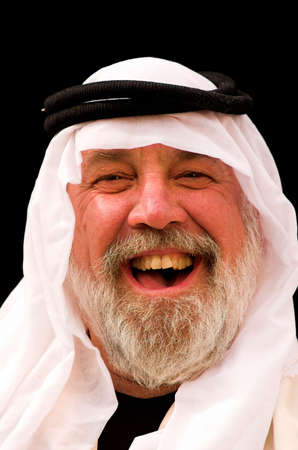 A laughing man wearing an Arabic headdress.