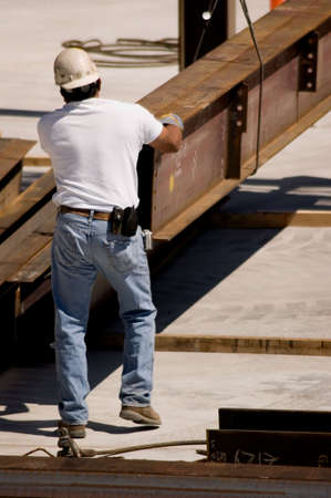 A construction worker handling an iron beam Imagens