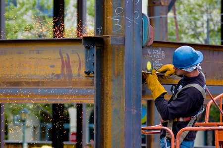 A construction worker welding an iron beam Imagens
