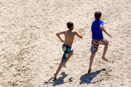 Two friends racing across a sandy beach in California