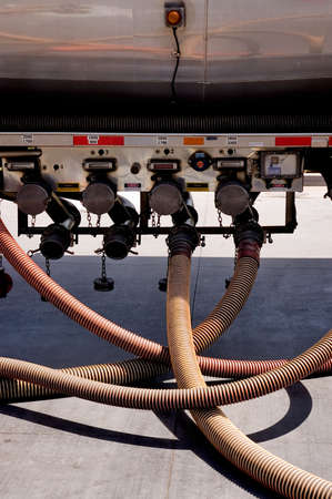A tangle of hoses coming from a gasoline tanker truck.