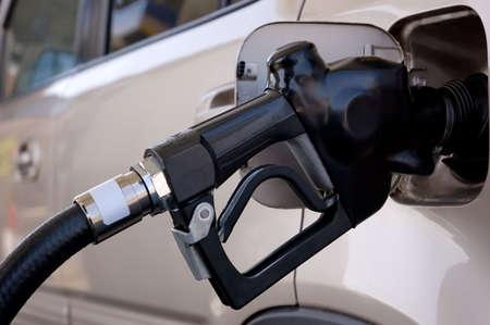 Closeup of a gasoline pump nozzle in the tank of a SUV