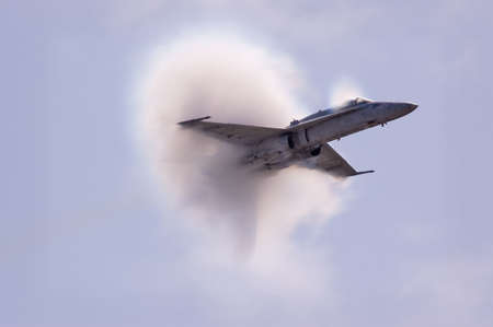 jet fighter: A condensation cloud caused by water particles condensing due to the sonic pressure waves from an aircraft