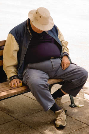 A heavy older gentleman who has fallen asleep on a city bench.