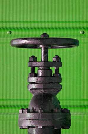 Black valve against a green corrugated wall