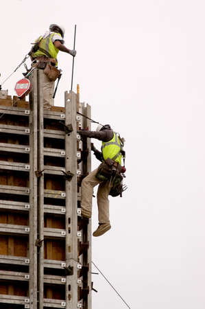 Workmen assembling a large form for a tall concrete wall. Stock Photo