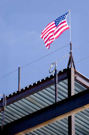 A United States flag raised by iron workers atop the structure they are building