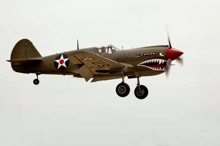 A World War II Curtiss P-40 airplane landing at an air show. Stock Photo
