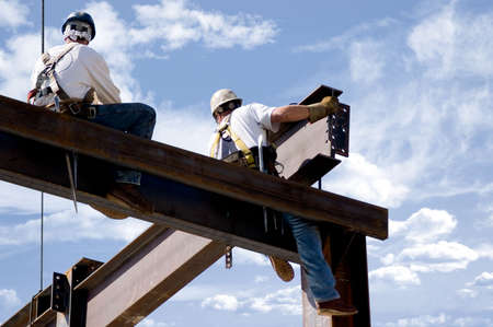 construction workers: Two ironworkers atop the skeleton of a modern building. One man is positioning a very large beam while the other watches.