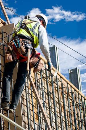 曇り空を背景に高い壁の上の建設労働者。 写真素材 - 1355410
