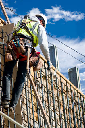 construction project: A construction worker on a high wall against a cloudy sky. Stock Photo