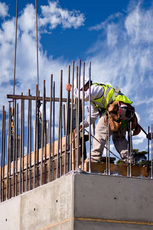 A construction worker guiding a section into place on a high concrete wall, shot against a cloudy sky.