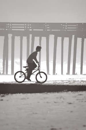 Greyscale summertime image of a boy riding his bicycle on a beach, with a wharf in the background. Stock Photo - 1413390