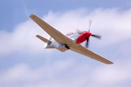 A restored P51 fighter airplane doing a fast flyby at an airshow photo