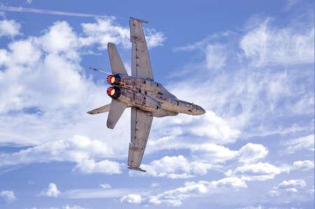 airpower: Un F-18 Hornet facendo girare un settore bancario nei confronti di un cielo nuvoloso.