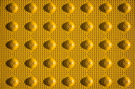 nonslip: Closeup of yellow non-slip curb ramp treads outside a grocery store.