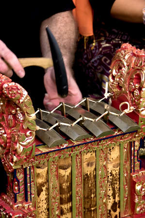 The hands of a gamelan player in motion