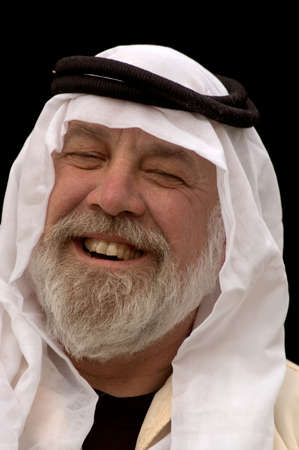 headress: A laughing man wearing an Arabic headdress, keffiyeh and agal.