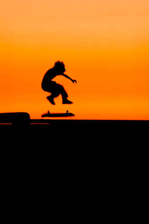 A boy making a high jump on his skateboard at sunset, silhouetted against a red sky.