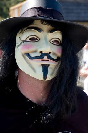 vengador: Un hombre en una celebraci�n que llevaba una m�scara, sombrero negro y capa Foto de archivo