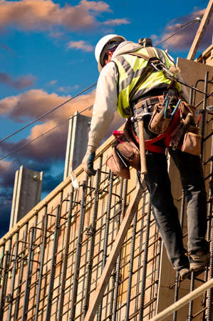 construction project: A construction worker on a high wall against colorful sunrise clouds. Stock Photo